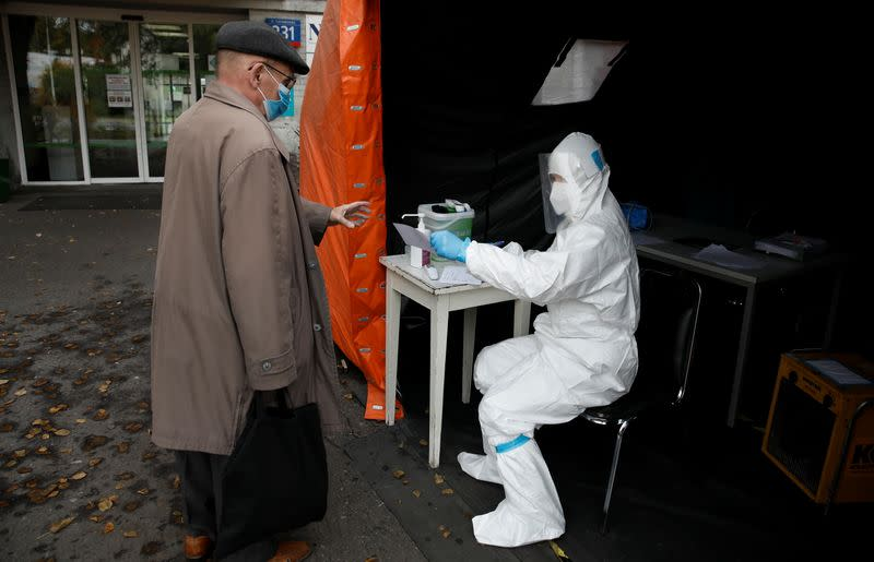 A health worker in protective suit gives a document to man in Warsaw