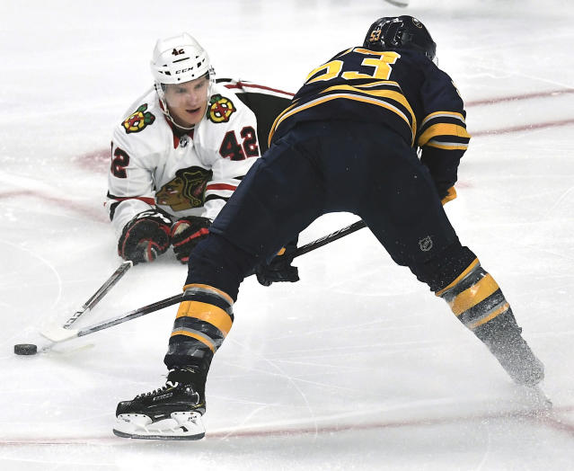 FILE - In this Feb. 1, 2019, file photo, Chicago Blackhawks defenseman Gustav Forsling (42) pokes the puck away from Buffalo Sabres center Jeff Skinner (53) during the third period of an NHL hockey game in Buffalo, N.Y. The Blackhawks have acquired defenseman Calvin de Haan in a trade with the Carolina Hurricanes. The Blackhawks also received minor league forward Aleksi Saarela from the Hurricanes in exchange for Forsling and goaltender Anton Forsberg. (AP Photo/Adrian Kraus, File)
