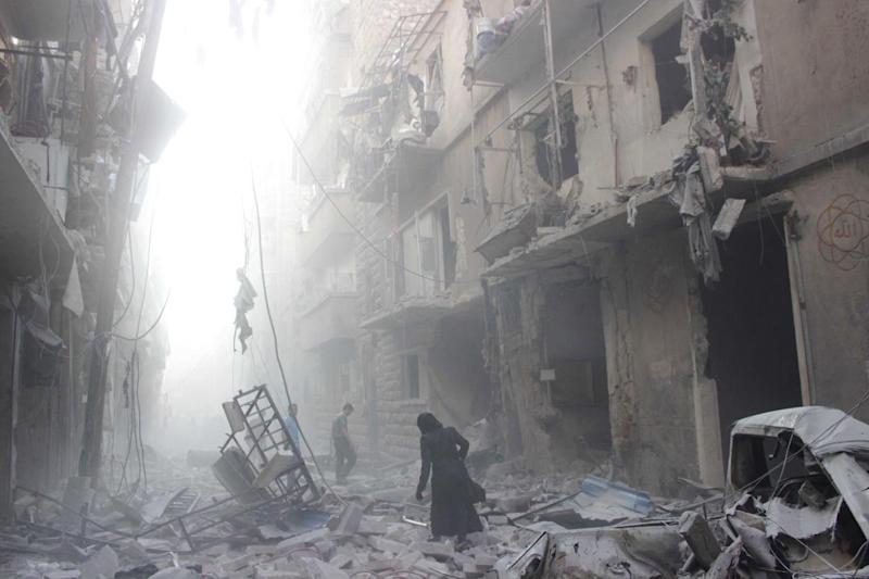A Syrian woman makes her way through debris following an air strike by government forces in the northern city of Aleppo on July 15, 2014