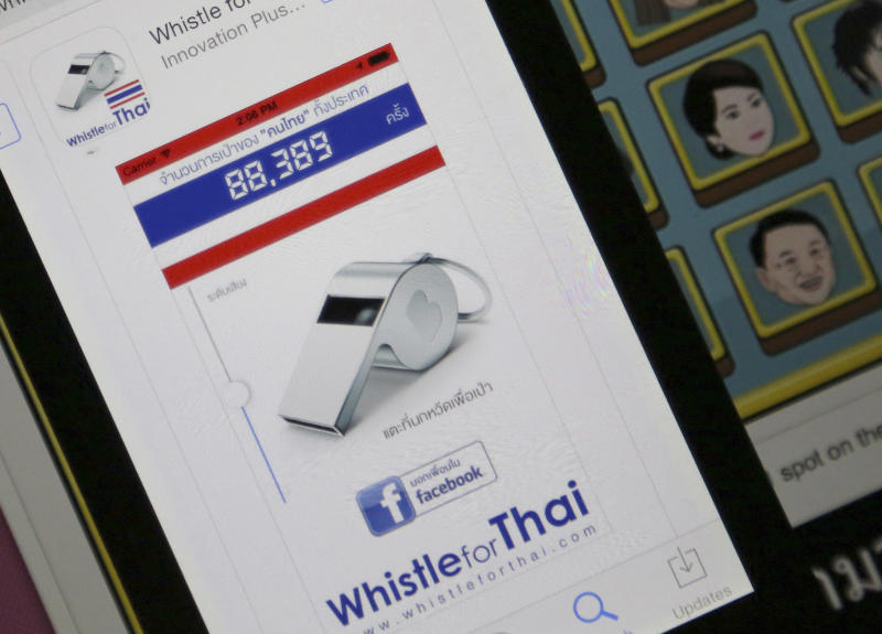 """Nok Weed, or Whistle, app is shown after being downloaded on a smartphone next to a computer screen that shows drawing pictures of Thai Prime Minister Yingluck Shinawatra, top right, and her brother former Prime Minister Thaksin Shinawatra, bottom right, Friday, Dec. 13, 2013 in Bangkok, Thailand. More than 70,000 people have downloaded one application that mimics the shrieking sound of a whistle - the symbol of the """"whistle-blowing campaign"""" against Yingluck. The new app is called """"Nok Weed"""" and it lets users choose the color of their whistle, adjust the volume and then tap the screen to sound it. (AP Photo/Apichart Weerawong)"""
