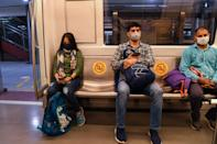 Commuters sit in a carriage of a Yellow Line train after Delhi Metro Rail Corporation (DMRC) resumed services following its closure due to the COVID-19 pandemic in New Delhi on September 7, 2020. (Photo by PRAKASH SINGH/AFP via Getty Images)