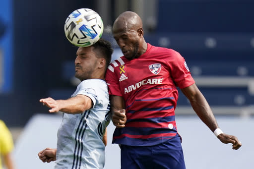 Sporting Kansas City defender Luis Martins, left, heads the ball against FC Dallas forward Fafa Picault, right, during the first half of an MLS soccer match in Kansas City, Kan., Saturday, Sept. 19, 2020. (AP Photo/Orlin Wagner)