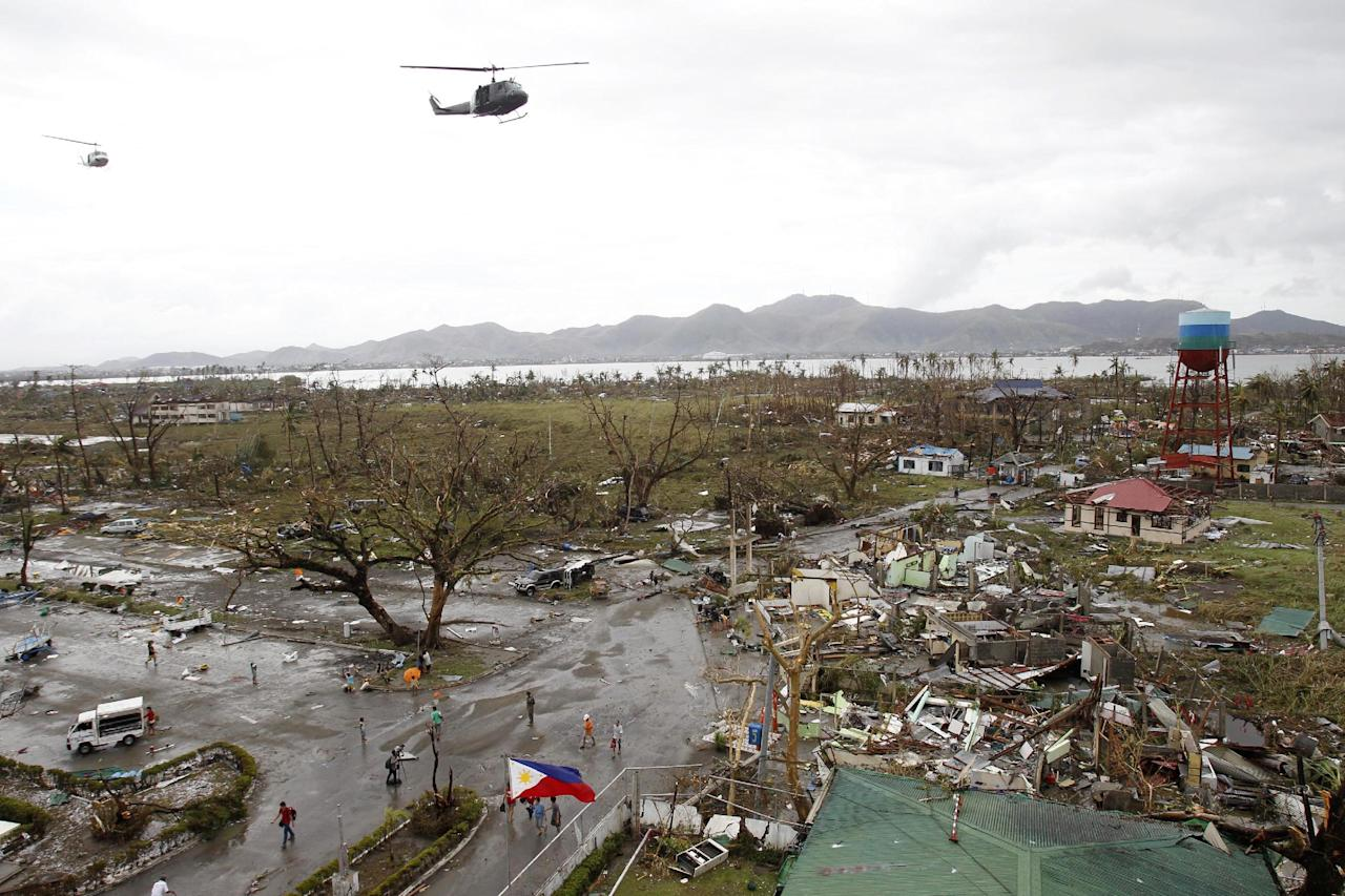 Helicopters hover over the damaged area after super Typhoon Haiyan battered Tacloban city, central Philippines, November 9, 2013. Possibly the strongest typhoon ever to hit land devastated the central Philippine city of Tacloban, killing at least 100 people, turning houses into rubble and leveling the airport in a surge of flood water and high wind, officials said on Saturday. The toll of death and damage from Typhoon Haiyan on Friday is expected to rise sharply as rescue workers and soldiers reach areas cut off by the massive, fast-moving storm which weakened to a category 4 on Saturday. REUTERS/Romeo Ranoco (PHILIPPINES - Tags: DISASTER ENVIRONMENT TPX IMAGES OF THE DAY)