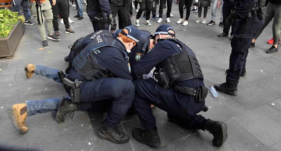 Protesters are arrested by the police at Sydney Town Hall during the anti-lockdown rally in Sydney, Saturday, July 24, 2021. Source: AAP
