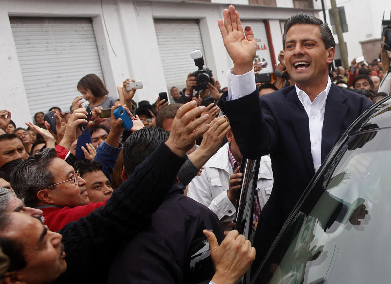 Enrique Pena Nieto, top, presidential candidate for the Revolutionary Institutional Party (PRI) waves to supporters after casting his vote during general elections at a polling station in Atlacomulco, Mexico, Sunday, July 1, 2012. Mexico's more than 79 million voters head to the polls Sunday to elect a president, who serves one six-year term, as well as 500 congressional deputies and 128 senators. (AP Photo/Esteban Felix)