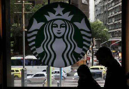 Customers pass by the logo of an American coffee company Starbucks inside a coffee shop in Rio de Janeiro