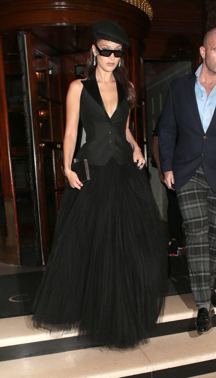 <p>Bella Hadid stepped out in London wearing a tulle black skirt and plunge-neck waistcoat for Dior's Backstage launch at Loulou's in May 2018. She teamed the Parisian-inspired look with dark black sunglasses and a beret accessorised with a black veil. Très chic, non?</p>