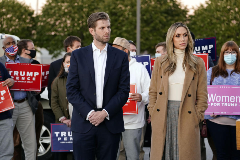 Eric Trump, son of President Trump, and wife Lara Trump listen as Rudy Giuliani, a lawyer for President Donald Trump, speaks off camera during a news conference on legal challenges to vote counting in Pennsylvania, Wednesday, Nov. 4, 2020, in Philadelphia. (AP Photo/Matt Slocum)
