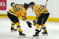 Boston Bruins right wing David Pastrnak (88) and center Patrice Bergeron (37) celebrate after an NHL hockey game against the New York Islanders, Thursday, April 15, 2021, in Boston. (AP Photo/Elise Amendola)