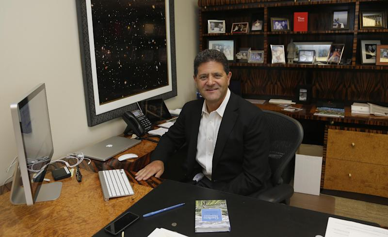 """In this Aug. 2, 2013 photo, Venture capitalist Nick Hanauer poses for a photo in his office in downtown Seattle. Washington state already has the nation's highest state minimum wage at $9.19 an hour, and Hanauer endorses calls to raise it, because he feels putting money in the hands of regular consumers could reduce the drop in demand for goods that he says has hurst our economy. Hanauer is holding a copy of """"Democracy: A Journal of Ideas,"""" that has an article in it he co-authored that promotes an economy driven by a strong middle class. (AP Photo/Ted S. Warren)"""