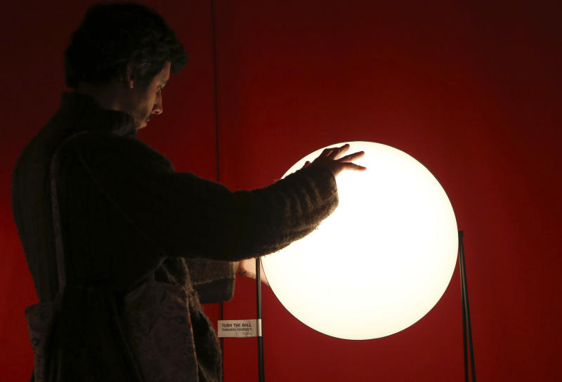 """A man touches a lamp called """"Light Sister"""" on display at the Milan Design Fair, in Milan, Italy, Thursday, April 11, 2013. The Milan furniture and design week fair, showcasing the latest in furniture and design from countries around the world, will continue until Sunday. (AP Photo/Antonio Calanni)"""