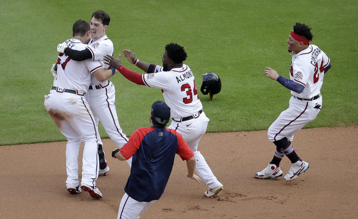 Atlanta Braves' Max Fried, second from left, is mobbed after making the game winning hit against the Miami Marlins during the tenth inning of a baseball game Sunday, July 4, 2021, in Atlanta. (AP Photo/Ben Margot)