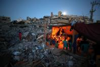 Palestinians from Zawaraa family hold candles as they sit in a makeshift tent amid the rubble of their houses which were destroyed by Israeli air strikes during the Israeli-Palestinian fighting in Gaza