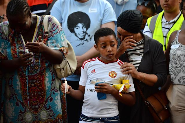 <p>Emotions run high as people attend a candle lit vigil outside Notting Hill Methodist Church near the 24 storey residential Grenfell Tower block in Latimer Road, West London on June 14, 2017 in London, England. (Photo: Chris J Ratcliffe/Getty Images) </p>