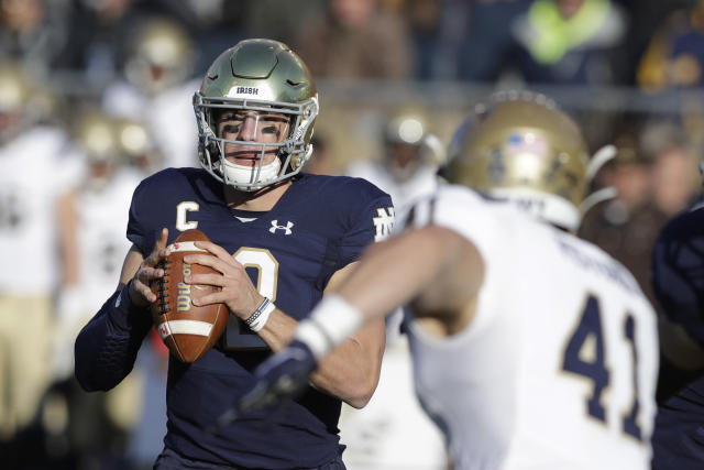 Notre Dame quarterback Ian Book (12) throws against Navy linebacker Tyler Pistorio (41) during the first half of an NCAA college football game, Saturday, Nov. 16, 2019, in South Bend, Ind. (AP Photo/Darron Cummings)