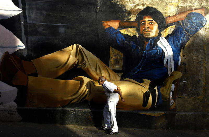 """In this April 23, 2013 photo, an elderly Indian man walks past a mural depicting Bolllywood superstar Amitabh Bachchan's as in a scene from film """"Deewar"""" in Mumbai, India. Friday, May 3 marks exactly a hundred years after India's first feature film """"Raja Harischandra,"""" a silent movie, was screened in 1913. India produced almost 1,500 movies last year and the industry is expected to grow from $ 2 billion to $ 3.6 billion in the next five years, according to consultancy KPMG. (AP Photo/Rafiq Maqbool)"""
