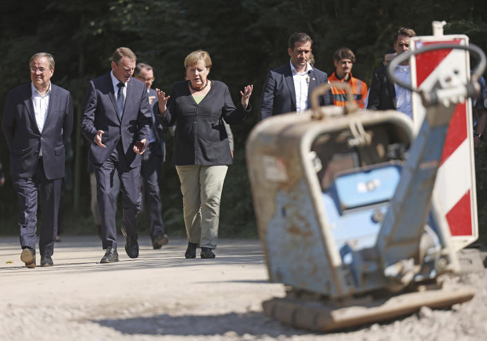 German Chancellor Angela Merkel, centre, walks with Armin Laschet, left, candidate for chancellor of the CDU/CSU and chairman of the CDU, and Fritz J'ckel, second from left, North Rhine-Westphalia's commissioner for reconstruction in flooded areas, as they vistit areas affected by flooding, in Hagen, Germany, Sunday, Sept. 5, 2021. (Oliver Berg/Pool Photo via AP)