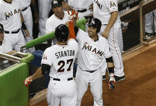 Miami Marlins' Placido Polanco, right, celebrates with Giancario Stanton, who hit a home run during the eighth inning of a baseball game against the San Diego Padres in Miami, Saturday, June 29, 2013. The Marlins won 7-1. (AP Photo/J Pat Carter)