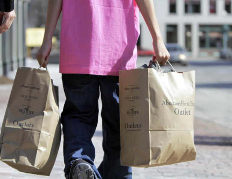 FILE - In this March 12, 2012 file photo, a shopper carries bags of merchandise in Freeport, Maine. U.S. retail sales rose at a solid pace in March 2012, as a healthier job market encouraged more consumers to shop, the Commerce Department said Monday, April 16, 2012. (AP Photo/Pat Wellenbach, File)