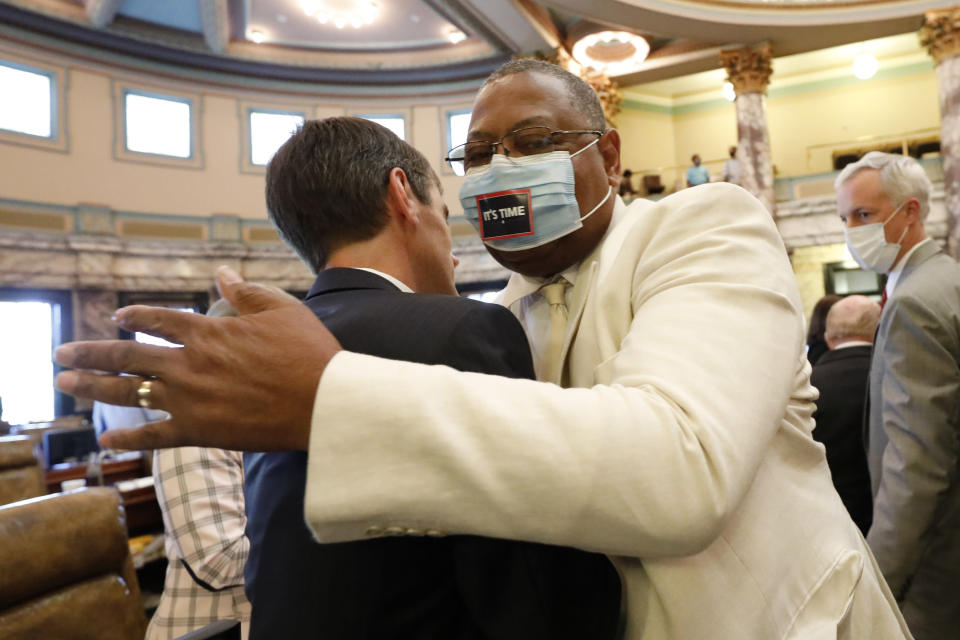 Sen. Briggs Hopson, left, R-Vicksburg, is hugged by Sen. Robert Jackson, D-Marks, after the Senate voted to change the state flag, Sunday, June 28, 2020, at the Capitol in Jackson, Miss. Hopson presented the bill to the body. Lawmakers in both chambers voted to surrender the Confederate battle emblem from their state flag. Republican Gov. Tate Reeves has said he will sign the bill. (AP Photo/Rogelio V. Solis)