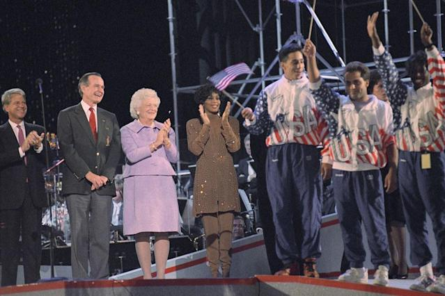 Georgia Olympians, right, celebrate, Thursday, Sept. 18, 1992 at the Georgia Dome in Atlanta for the arrival of the Olympic flag to Atlanta. President Bush, first lady Barbara Bush and entertainer Whitney Houston join in the activity. Atlanta will host the 1996 Summer Olympics. (AP Photo/J. Scott Applewhite)