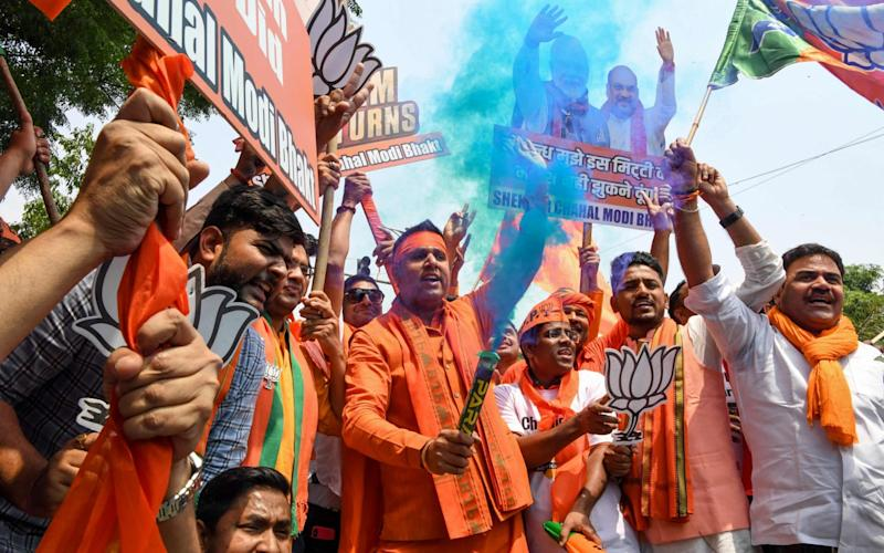 Indian Bharatiya Janata Party (BJP) supporters hold colour smoke crackers as they celebrate on the vote results - AFP