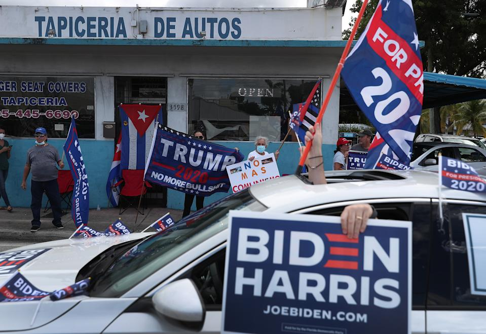 MIAMI, FLORIDA - OCTOBER 18: A caravan of supporters for Democratic presidential nominee Joe Biden drive past supporters of President Donald Trump standing on the sidewalk next to the Versailles Restaurant during a Worker Caravan for Biden event on October 18, 2020 in Miami, Florida. The caravan was part of a countywide caravan put together by union workers, activists and supporters of Joe Biden the day before polls opened for early voting in the general election. (Photo by Joe Raedle/Getty Images)