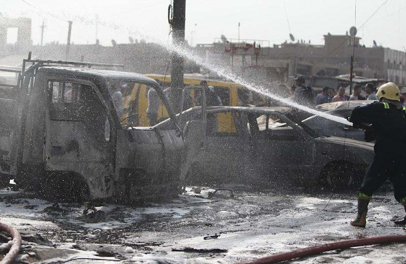 A member of the Iraqi emergency services extinguishes smoke at the site of a car bomb explosion in a commercial district of new Baghdad on August 26, 2014