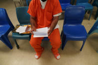 Immigration detainee Alexander Martinez shows his handwritten notations of allegations of abusive treatment, as he speaks during an interview with The Associated Press inside the Winn Correctional Center in Winnfield, La., Friday, July 30, 2021. (AP Photo/Gerald Herbert)
