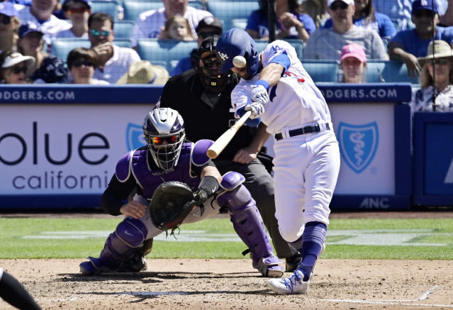Los Angeles Dodgers' Chris Taylor, right, hits a three-run home run as Colorado Rockies catcher Tony Wolters, left, watches along with home plate umpire Paul Emmel, center, during the seventh inning of a baseball game Sunday, June 23, 2019, in Los Angeles. (AP Photo/Mark J. Terrill)