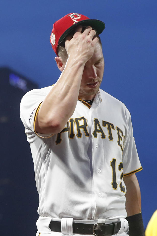 Pittsburgh Pirates left fielder Corey Dickerson wipes his head as he leaves the baseball game after catching a fly ball by Milwaukee Brewers' Yasmani Grandal during the seventh inning Saturday, July 6, 2019, in Pittsburgh. (AP Photo/Keith Srakocic)