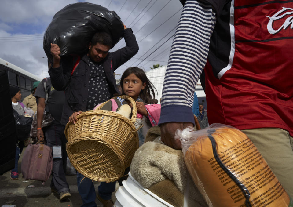 Brittany Rios, of Honduras, center, carries stuffed animals in a wicker basket as her family leaves a shelter for members of the Central American migrant caravan in Tijuana, Mexico, Friday, Nov. 30, 2018. Authorities in Tijuana said Friday they have begun moving Central American migrants from an overcrowded shelter on the border to an events hall further away. (AP Photo/Gregory Bull)