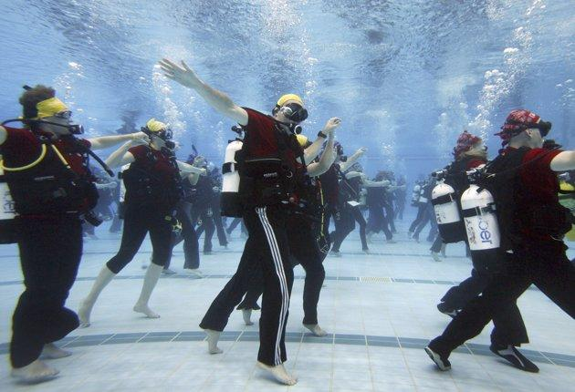 Seventy-four scuba divers dance to set the world record for an underwater dance class at Sydney's Olympic Park Aquatic Centre October 27, 2006. The divers were required to dance simultaneously for ten minutes to set the record, with the event also raising money for charity. REUTERS/David Gray