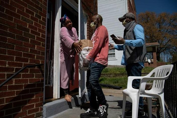 Anthony Lorenzo Green (R) and Bernard Stevenson (C) deliver groceries to a woman in Washington during the coronavirus pandemic (AFP Photo/NICHOLAS KAMM)