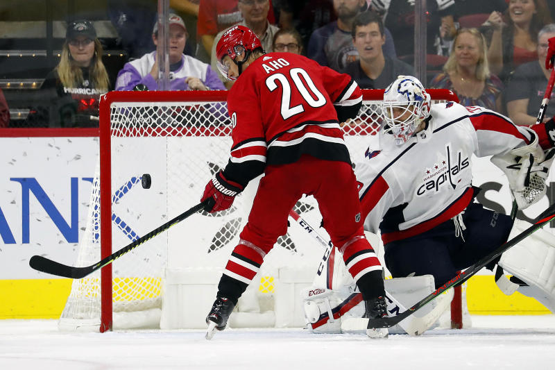 Carolina Hurricanes' Sebastian Aho (20), of Finland, knocks the puck out of the air and past Washington Capitals goaltender Braden Holtby (70) during the third period of an NHL preseason hockey game in Raleigh, N.C., Sunday, Sept. 29, 2019. (AP Photo/Karl B DeBlaker)
