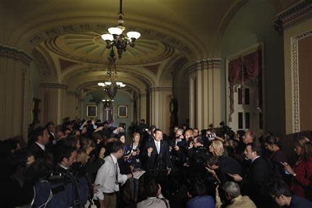 Reporters gather around U.S. Senator Cruz as he announces he will not filibuster, after a Republican Senate caucus meeting at the U.S. Capitol in Washington