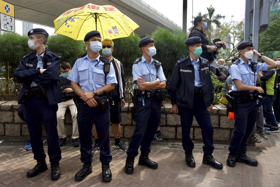 Police officers stand guard as supporters queue up outside a court to try get in for a hearing in Hong Kong Monday, March 1, 2021. People gathered outside the court Monday to show support for 47 activists who were detained over the weekend under a new national security law that was imposed on the city by Beijing last year. (AP Photo/Vincent Yu)