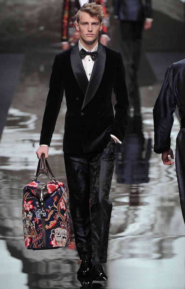 <p>Model wears a smooth midnight blue velvet blazer with printed trousers and colorful weekender bag. <br> (Photo: Catwalking) </p>