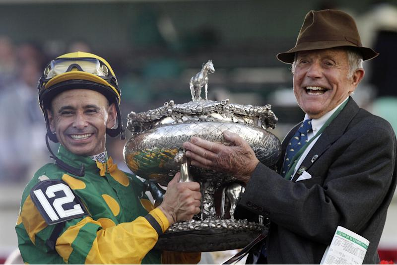 Jockey Mike Smith, left, and Cot Campbell, President of Dogwood Stables, hold the Belmont Stakes trophy in the winner's circle after Smith rode Palace Malice to win the Belmont Stakes horse race in Elmont, N.Y., Saturday, June 8, 2013. (AP Photo/Mark Lennihan)