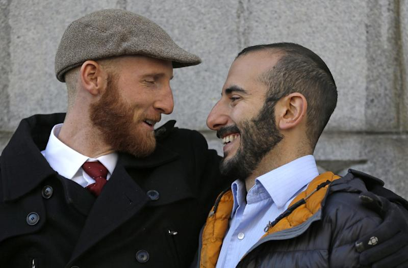 FILE - In this Dec. 4, 2013, file photo, Derek Kitchen, left, and his partner Moudi Sbeity hug each other outside Frank E. Moss United States Courthouse, in Salt Lake City. The young couple that has become the face of gay marriage in Utah is an unlikely pair for the role. Kitchen and Sbeity were both raised in conservative religious families that shun gays, Kitchen in a Mormon home in Utah and Sbeity in a Muslim family in Lebanon. They each came out when they were 16 years old, worlds apart, and met six years later in college in Utah. They chose to become one of three couples as plaintiffs in the lawsuit challenging Utah's same-sex marriage to publicly push back against religions that oppress gays and lesbians. (AP Photo/Rick Bowmer, File)