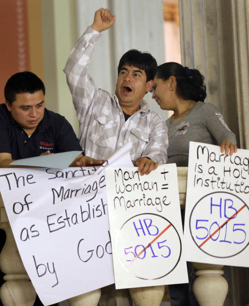 A demonstrator displays a placard and gestures as he joins with others opposed to same-sex marriage during a rally at the Statehouse, in Providence, Tuesday, Jan. 15, 2013. The Rhode Island House Judiciary Committee began hearing testimony from supporters and opponents of same-sex marriage Tuesday. (AP Photo/Steven Senne)