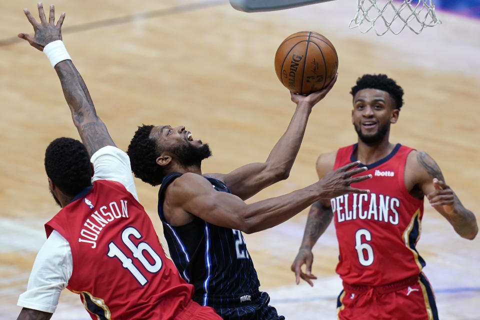 Orlando Magic guard Chasson Randle goes to the basket between New Orleans Pelicans forward James Johnson (16) and guard Nickeil Alexander-Walker (6) during the second half of an NBA basketball game in New Orleans, Thursday, April 1, 2021. (AP Photo/Gerald Herbert)