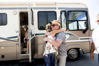 Woody Faircloth hugs Sheri Roen as her family donates their motorhome to EmergencyRV.org on Sunday, Sept. 5, 2021, in Sierra County, Calif. Accompanied by daughter Luna, left, Faircloth delivered it to a Dixie Fire victim later that day, (AP Photo/Noah Berger)