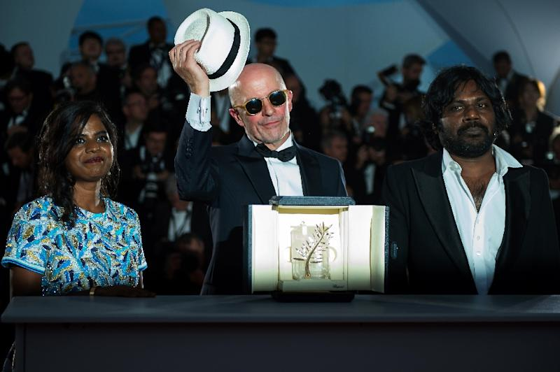 """Director Jacques Audiard (C) poses with Sri Lankan actors Kalieaswari Srinivasan (L) and Jesuthasan Antonythasan after being awarded with the Palme d'Or for """"Dheepan"""" during the 68th Cannes Film Festival in Cannes, France, on May 24, 2015 (AFP Photo/Bertrand Langlois)"""