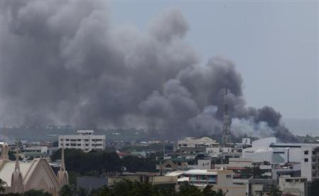 Smoke billows from downtown Zamboanga city as fighting rages between government soldiers and the Muslim rebels of the Moro National Liberation Front (MNLF), in southern Philippines September 19, 2013. REUTERS/Erik De Castro