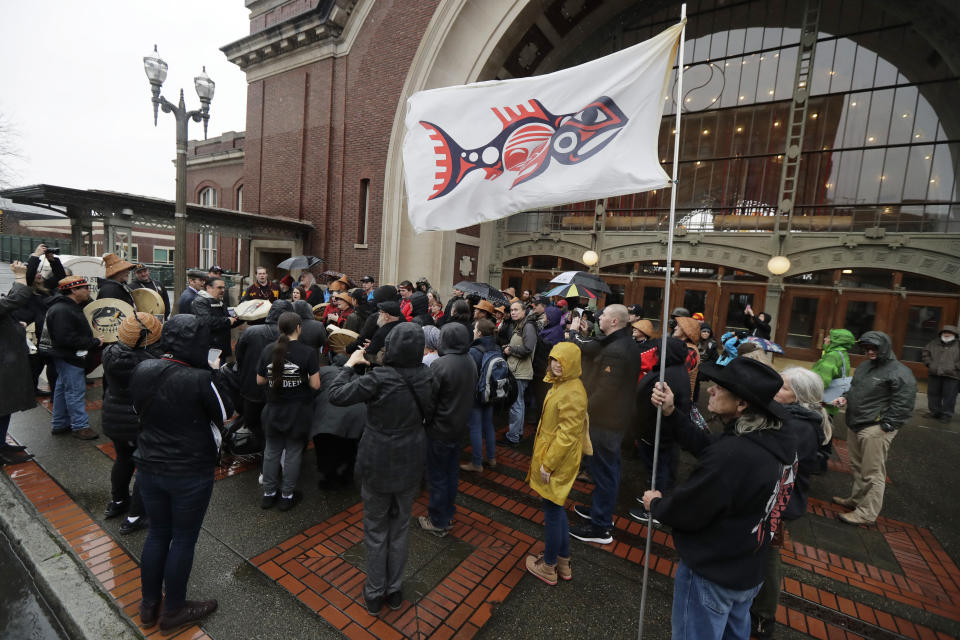 FILE - In this Jan. 6, 2020, file photo, the flag of the Chinook Indian Nation is displayed in the wind as tribal members and other supporters gather outside the federal courthouse in Tacoma, Wash., as they continue their efforts to regain federal recognition. As COVID-19 disproportionately affects Native American communities, many tribal leaders say the pandemic poses particular risks to tribes without federal recognition. (AP Photo/Ted S. Warren, File)