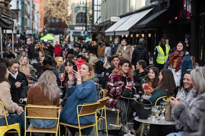 LONDON, UNITED KINGDOM - APRIL 12, 2021: Crowds fill tables in Old Compton Street in Soho, which is closed to traffic, as outdoor hospitality venues open their premises to customers after being closed for over three months under coronavirus lockdown, on 12 April, 2021 in London, England. From today the next stage of lifting lockdown restrictions goes ahead with pubs and restaurants allowed to serve food and drinks outdoors, opening of non-essential shops, hairdressers, beauty salons and gyms in England. (Photo credit should read Wiktor Szymanowicz/Barcroft Media via Getty Images)