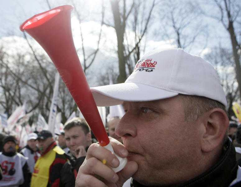 Polish workers protesting a government plan to raise retirement age to 67, turn their backs to a screen, not seen, showing Prime Minister Donald Tusk speaking about the plan in Parliament, in Warsaw, Poland on Friday, March 30, 2012. (AP Photo/Czarek Sokolowski)