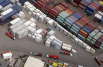 FILE PHOTO: Trucks and workers load containers onto trucks at a container terminal in Sydney, Australia