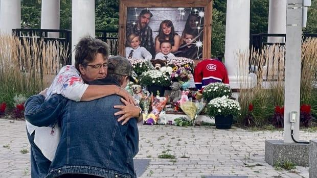 Family members of six people who died after their camper trailer caught fire in rural Nova Scotia comfort each other in front of a memorial at a park in Amherst, N.S. (Steve Lawrence/CBC - image credit)